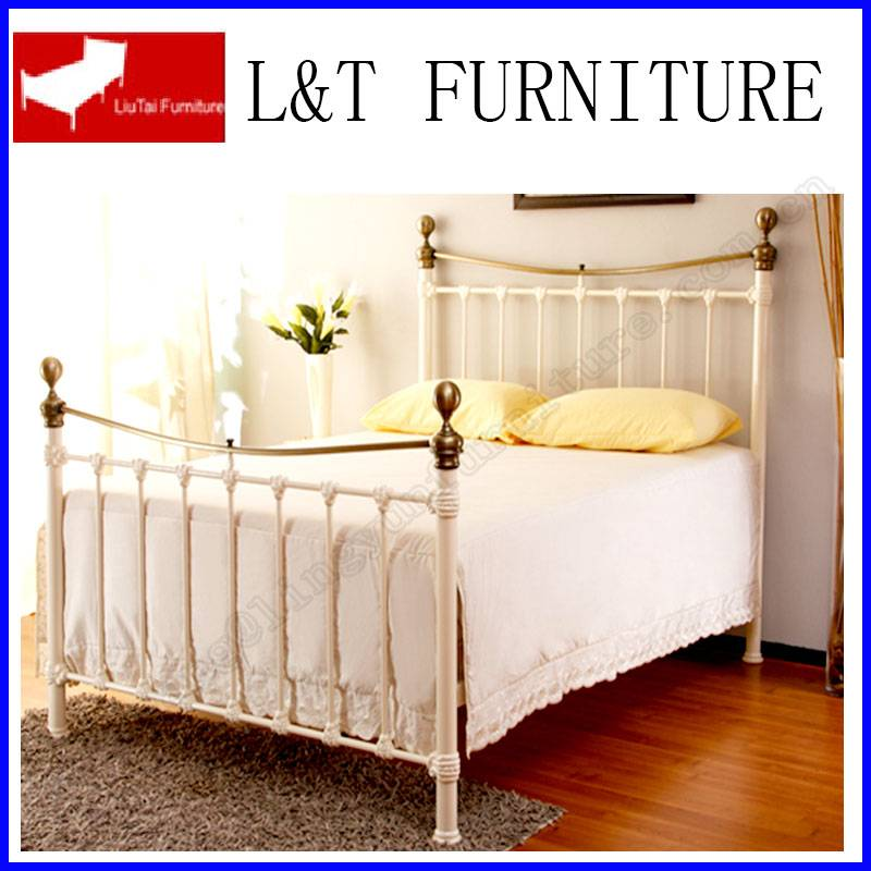 white metal bed with golden ball