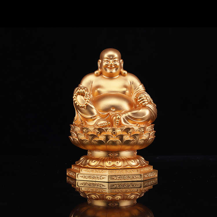 The golden happy buddha stuatue is seated in a double lotus base show his smiling and big belly